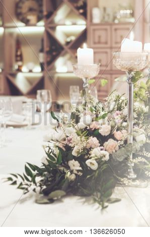 Blurred background stylish fashionable wedding celebration wallpaper floral background. Elegance table set in banquet restoraunt with elegant floral composition of beige and pink roses eustoma carnations peony flowers. Place for text free copy space.