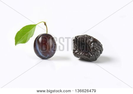 one fresh plum and one prune on white background