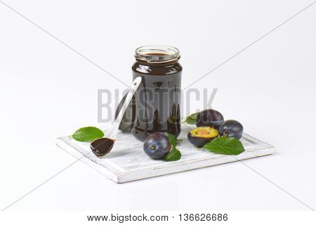 jar of thick plum butter and fresh plums next to it