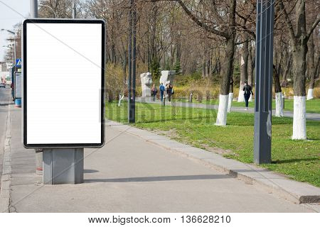 Empty billboard or lightbox on green city street with white isolated background