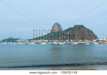 Mountain Sugarloaf and yachts in Guanabara bay from Botafogo beach in rainy day Rio de Janeiro. Selective focus. Toning effect