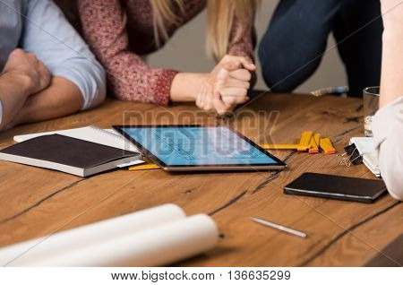 Group of architects working together on a project. Architect getting approval of client for house plan. Group of designer working on digital tablet.
