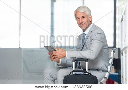 Happy successful businessman working on digital tablet while waiting at the airport lounge. Portrait of senior business man in formal checking mails on laptop and looking at camera