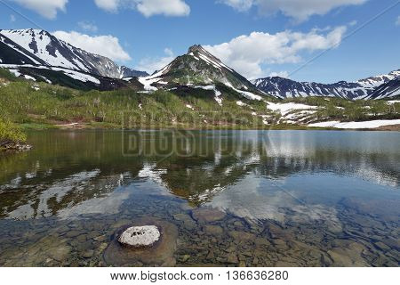 Summer landscape of Kamchatka Peninsula: beautiful view of Mountain Range Vachkazhets mountain lake and clouds in blue sky on sunny day. Eurasia Far East Russia Kamchatsky Region.