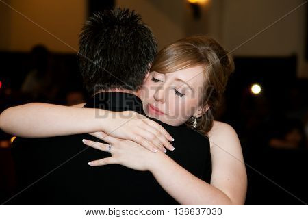 A bride hugs her father at the end of the father daughter dance at her wedding reception.