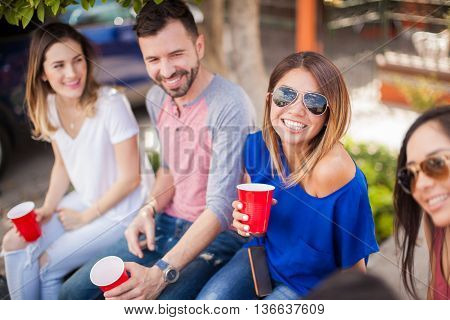 Beautiful young woman drinking beer with her friends at a game and having some fun