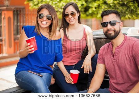 Three attractive young friends wearing sunglasses and drinking beer while hanging out on a sunny day in summer