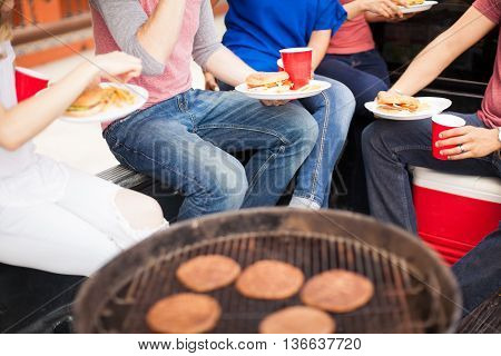 Friends Eating Burgers At A Barbecue