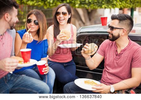 Four good looking Hispanic friends having fun while eating cheeseburgers and drinking beer outdoors at a barbecue