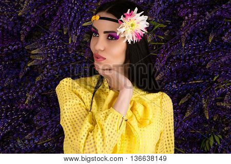 woman in yellow on background lupine flowers