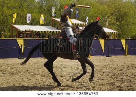 The horse knight in an armour and in a helmet with a sword in a hand. St.George knightly tournament. Moscow on May 1 2016 poster
