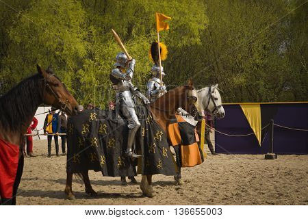 The horse knights in an armour and in a helmet with a sword in a hand. St.George knightly tournament. Moscow on May 1 2016 poster