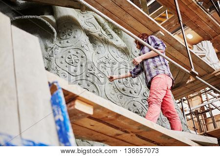 RUSSIA, MOSCOW - MAY 28, 2015: Female employee works on fragment of clay sculpture to St. Vladimir in the workshop of sculptor Salavat Shcherbakov. Monument will be installed at Borovitskaya square.