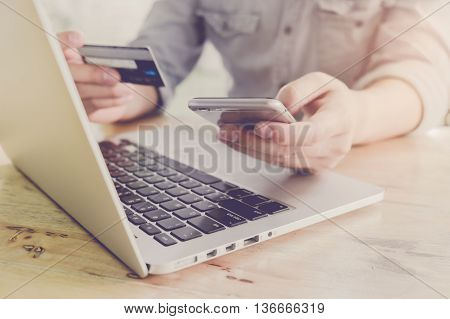 Online paymentMan's hands holding a credit card and using smart phone for online shopping with vintage filter effect