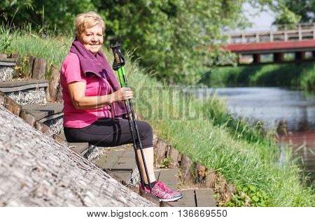 Senior Woman Resting After Nordic Walking On Riverside, Sporty Lifestyles