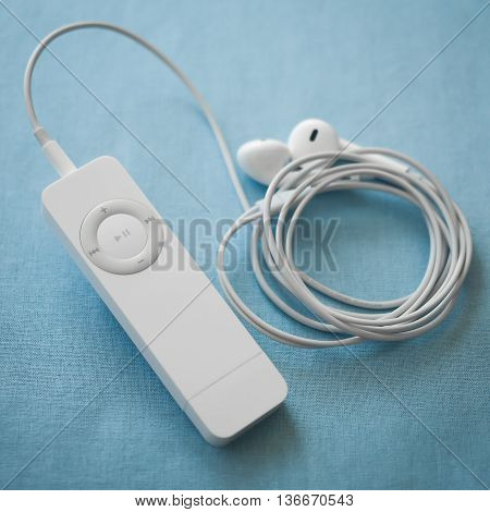 BERRY AUSTRALIA - June 28 2016 : An Apple iPod Shuffle first generation with Apple Earpods attached on a plain blue background.