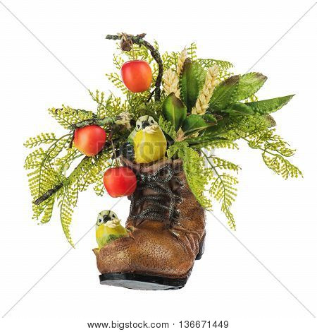 Table floral arrangement made of artificial flowers and fruits in stylized ceramic vase in the form of an old shoe with two birdies holding in its beak ears of wheat isolated on white background. poster