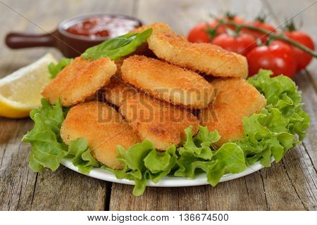 Traditional chicken nuggets on a wooden background