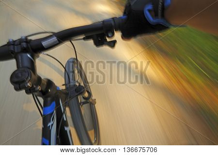 Front part of a fast motion mountain bike on a shady road