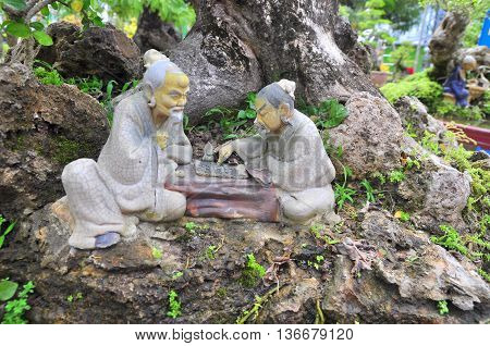 Statues of Confucius philosopher are playing chess