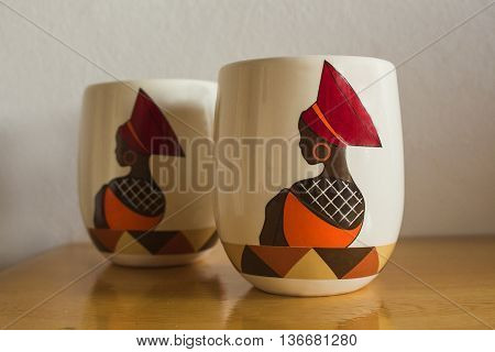 Coffee mugs. Traditional African style. Craftsmanship. Image beautiful African woman in ethnic clothes and hat. Souvenirs.