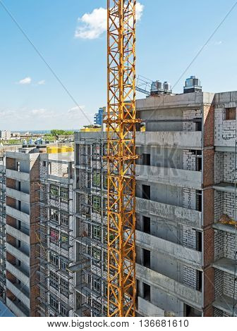 Side of of a house construction high-rise multilevel building with right angles amid crane