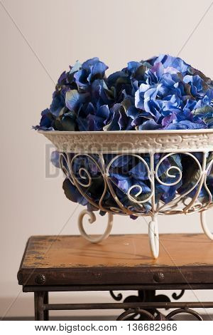 flowers of blue hydrangeas in a metal florid forged vase on stools