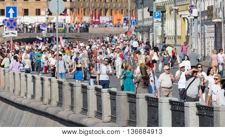 Moscow - May 9 2016: A lot of people and tourists walking on the embankment of the Moskva River after the Victory Parade and share Immortal regiment of May 9 2016 Moscow Russia