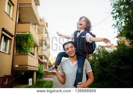 Little pupil sitting on the shoulders of his father. He placed his hands to the sides as if flying. Dad and son a great mood. They play on the way to school. Behind the schoolboy's backpack.