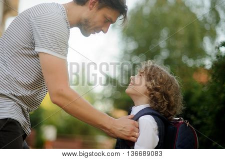 The father sends in school of the son-first-grader. It carefully corrects for a backpack of the boy. The small student looks at the daddy with love. It smiles.