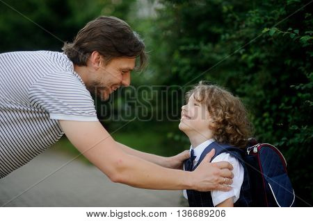 The father sees off the son-schoolboy in school. It has bent to the boy and has taken it for shoulders. The father and the son look against each other with love and smile.