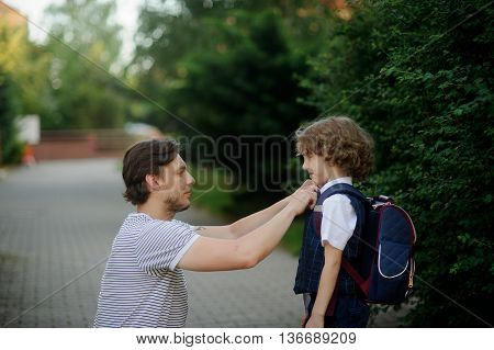 The father sees off the son-first-grader in school. It has sat down near to the boy and carefully corrects for its clothes. The boy looks at the daddy with love and smiles.