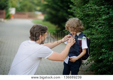 The father accompanies his son-grader to school. He sat down next to the boy and carefully straightens his clothes. A boy looks at dad and happy laughs.