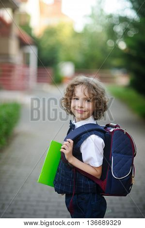 Little Kinky schoolboy stands in the courtyard of the school. The boy's cute face. Behind the backpack in the hands of bright green folder. Boy looks into the camera and smiles.