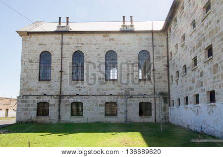 FREMANTLE,WA,AUSTRALIA-JUNE 1,2016:  Fremantle Prison  with its old limestone brick architecture and arched windows under a blue sky Fremantle, Western Australia.