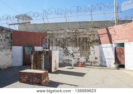 FREMANTLE,WA,AUSTRALIA-JUNE 1,2016:  Fremantle Prison yard with razor wire and weathered limestone walls with guard tower under a blue sky in Fremantle, Western Australia.