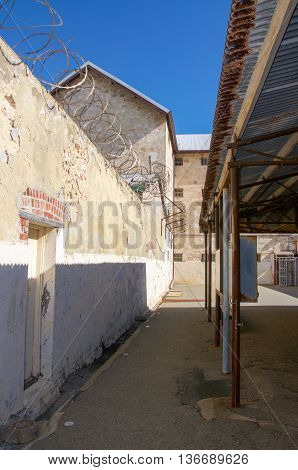 FREMANTLE,WA,AUSTRALIA-JUNE 1,2016:  Fremantle Prison outdoor boundary courtyard walls with razor wire under a blue sky in Fremantle, Western Australia.