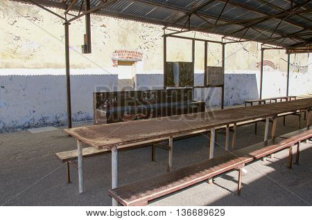 FREMANTLE,WA,AUSTRALIA-JUNE 1,2016: Outdoor yard with shelter, sink and long weathered table at the Fremantle Prison in Fremantle, Western Australia.