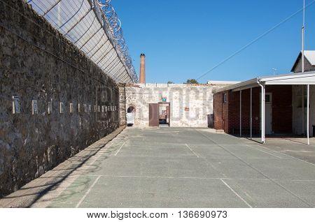 FREMANTLE,WA,AUSTRALIA-JUNE 1,2016:  Fremantle Prison with limestone brick walls and razor wire under a blue sky in Fremantle, Western Australia.