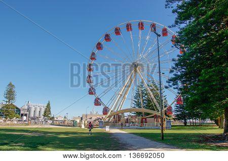 FREMANTLE,WA,AUSTRALIA-JUNE 1,2016: Ferris Wheel and tourists in the outdoor park setting no the esplanade in Fremantle, Western Australia.