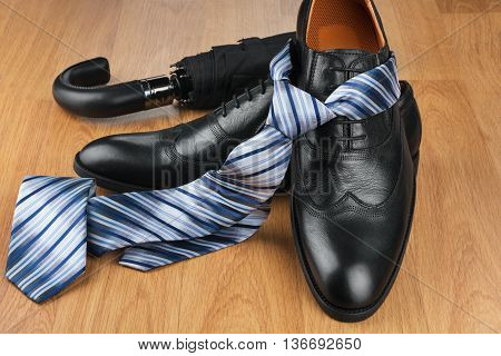 Classic mens black shoes tie umbrella on wooden floor can be used as background