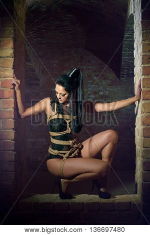Submissive sexy kneeling woman in the old room with brick walls