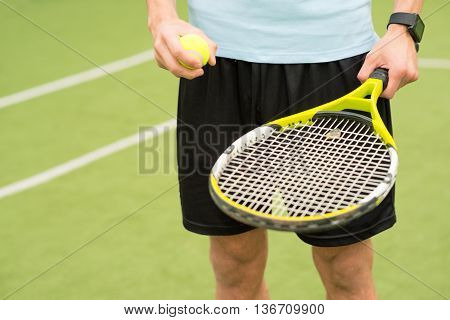 Close up of male hands holding tennis racket and ball. Man is standing on tennis court