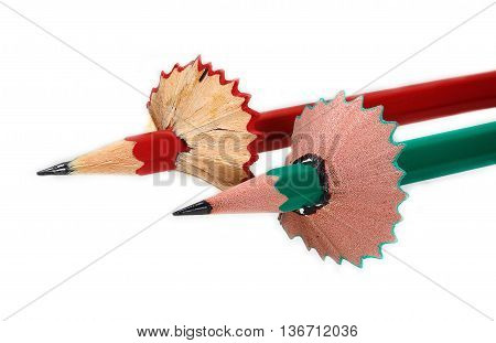 Red and green pencils with petticoats from shavings on white bacground