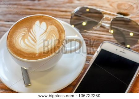 cup of the latte art coffee with spoon and plate on the brown bark beautiful texture background with warm light decorated with sunglasses