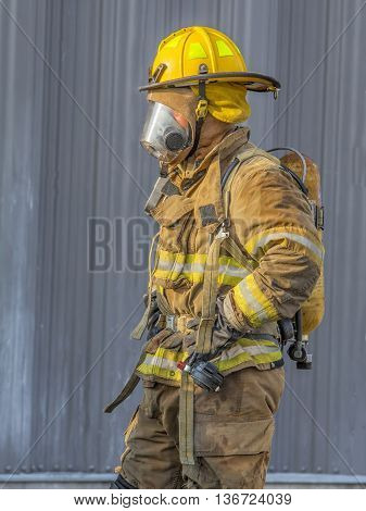A fireman dressed in his protective gear ready to fight a fire.