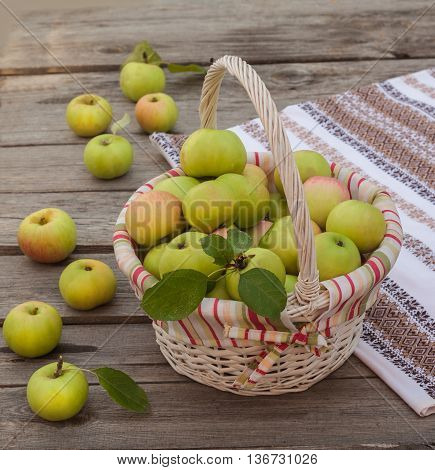 Rural autumn still life with a basket with apples on wooden table
