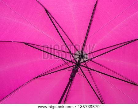 Close-up detail of the underside of a pink umbrella. Weather and forecast concept.