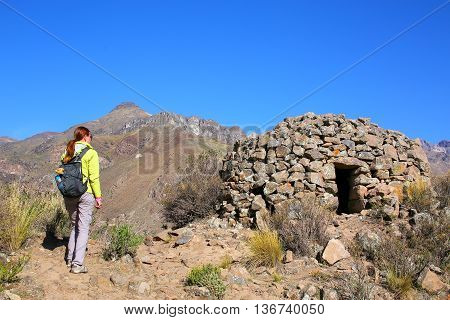 Tourist looking at pre-Incan round house named colca near Chivay in Peru. Colcas are circular stone structures used for food storage or burials.