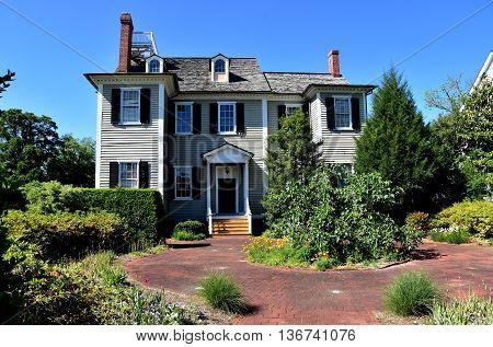 New Bern North Carolina - April 24 2016: Wooden gray clapboard 1835 Dixon House and garden courtyard at Tryon Palace